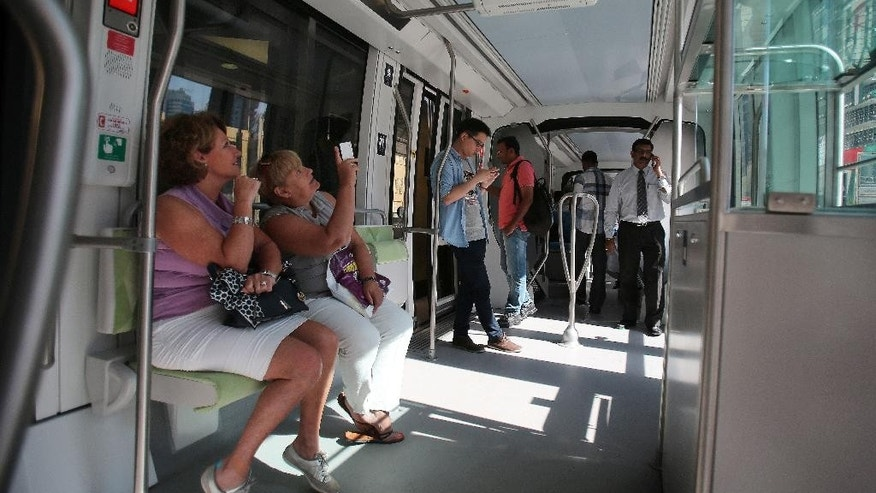 Passengers use the tram during its first day of operation in Dubai, United Arab Emirates, Wednesday, Nov. 12, 2014. The car-loving Mideast commercial hub of Dubai has opened its first tram line, enticing would-be riders with air-conditioned stations and a premium section on its sleek cars for big-spending commuters. (AP Photo/Kamran Jebreili)