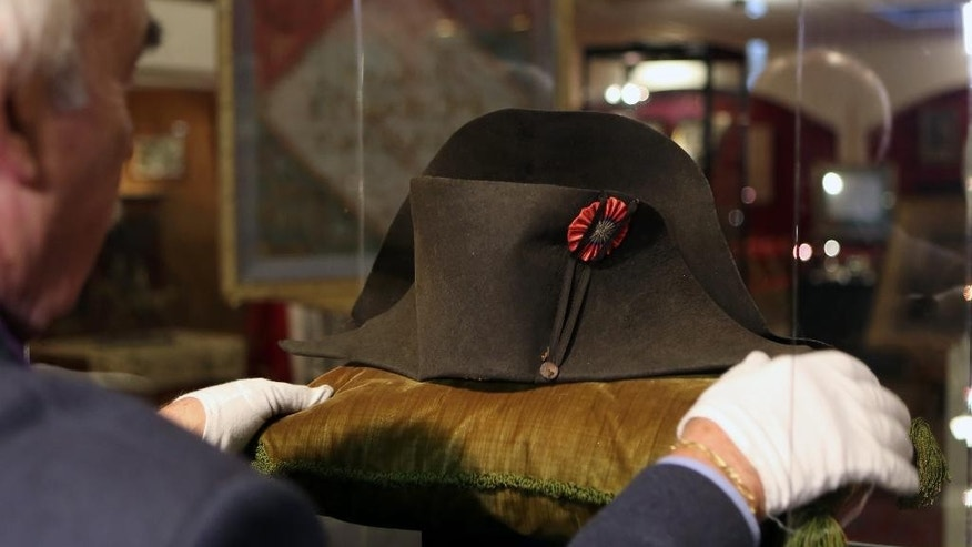Napoleon expert Jean Claude Dey sets up  Napoleon's hat, from the Napoleonic collection of the Palais de Monaco, in Fontainebleau, south of Paris, France, Wednesday Nov. 12, 2014. The hat is part of the Napoleonic collection gathered by Prince Louis II, that will be put on sale Nov. 15 and Nov. 16 in Fontainbleau. More than 1,000 objects among which is Napoleon's hat, will be put on sale at this auction. Napoleon bicorn hat is on display next to the chateau where the general lived when he wasn't leading troops into battle across Europe.  The felt is a little weathered by age and use, though no one's worn it since Napoleon's veterinarian, who received from the French leader as a gift, but auctioneers are hoping to fetch 500,000 euros ($623,000) for it at the weekend auction. (AP Photo/Remy de la Mauviniere)