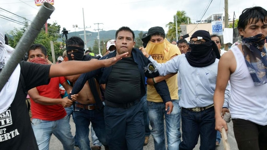 Masked teachers detain a police officer during clashes in Chilpancingo, the capital of Guerrero state, Mexico, Tuesday, Nov. 11, 2014. Supporters of 43 missing college rural students, refusing to believe they are dead, have kept up the protests that have blocked major highways and set government buildings ablaze in recent weeks. The students disappeared at the hands of a city police force on Sept. 26 in the town of Iguala. (AP Photo/Alejandrino Gonzalez)