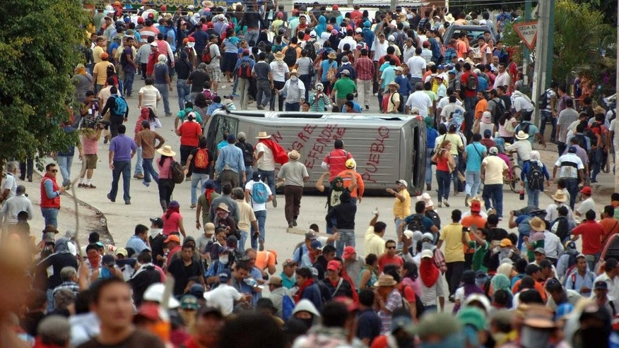 Teachers march around a vehicle they flipped during clashes with riot police in Chilpancingo, the capital of Guerrero state, Mexico, Tuesday, Nov. 11, 2014. Supporters of 43 missing college rural students, refusing to believe they are dead, have kept up the protests that have blocked major highways and set government buildings ablaze in recent weeks. The students disappeared at the hands of a city police force on Sept. 26 in the town of Iguala in Guerrero state. (AP Photo/Alejandrino Gonzalez)