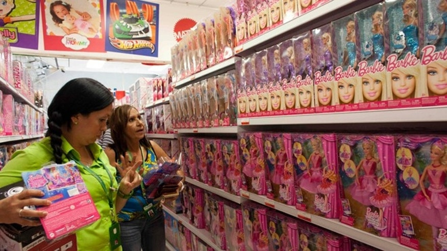 Shoppers look at the selection of Barbie dolls for sale at a store in Caracas, Venezuela, Monday, Nov. 10, 2014. Venezuelans are grabbing armfuls of the dolls in toy stores across Caracas, taking advantage of the governmentâs mandate that large chains sell the plastic figurines at fire-sale prices during the holiday shopping season. (AP Photo/Ariana Cubillos)