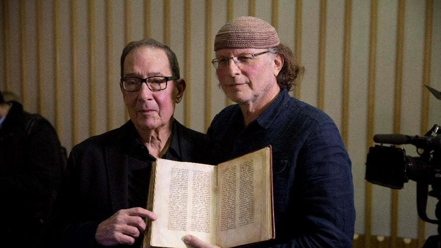 "Canadian-Israeli documentary film-maker and writer Simcha Jacobovici, right, and religious studies professor Barrie Wilson, the authors of ""The Lost Gospel"" pose for photographs after giving a press conference with a copy of an ancient manuscript at the British Library in London, Wednesday, Nov. 12, 2014.  A researcher who has attracted attention and criticism with revisionist Biblical theories says he has found new evidence that Jesus was married to Mary Magdalene and that early Christians considered her a deity.  Jacobovici says an ancient manuscript in the British Library relates the story of Jesus, his wife Mary Magdalene and their children.  He and Wilson outline their theory in ""The Lost Gospel"", published Wednesday.  (AP Photo/Matt Dunham)"