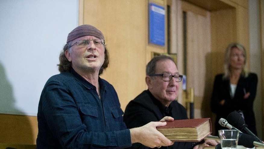 "Canadian-Israeli documentary film-maker and writer Simcha Jacobovici, left, holds a copy of an ancient manuscript as he and Canadian religious studies professor Barrie Wilson give a press conference for their book ""The Lost Gospel"" at the British Library in London, Wednesday, Nov. 12, 2014.  A researcher who has attracted attention and criticism with revisionist Biblical theories says he has found new evidence that Jesus was married to Mary Magdalene and that early Christians considered her a deity.  Jacobovici says an ancient manuscript in the British Library relates the story of Jesus, his wife Mary Magdalene and their children.  He and Wilson outline their theory in ""The Lost Gospel"", published Wednesday.  (AP Photo/Matt Dunham)"
