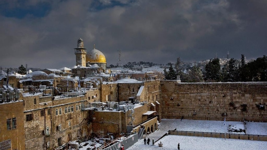 File - In this Dec. 13, 2013 file photo, the Western Wall, right, and the gilded Dome of the Rock, among the holiest sites for Jews and Muslims, are covered in snow. The trapezoid-shaped compound, known to Muslims as the Noble Sanctuary and to Jews as the Temple Mount, is at the heart of the territorial and religious conflict between Israel and its Arab neighbors. It has been the site of recent unrest. (AP Photo/Dusan Vranic, File)