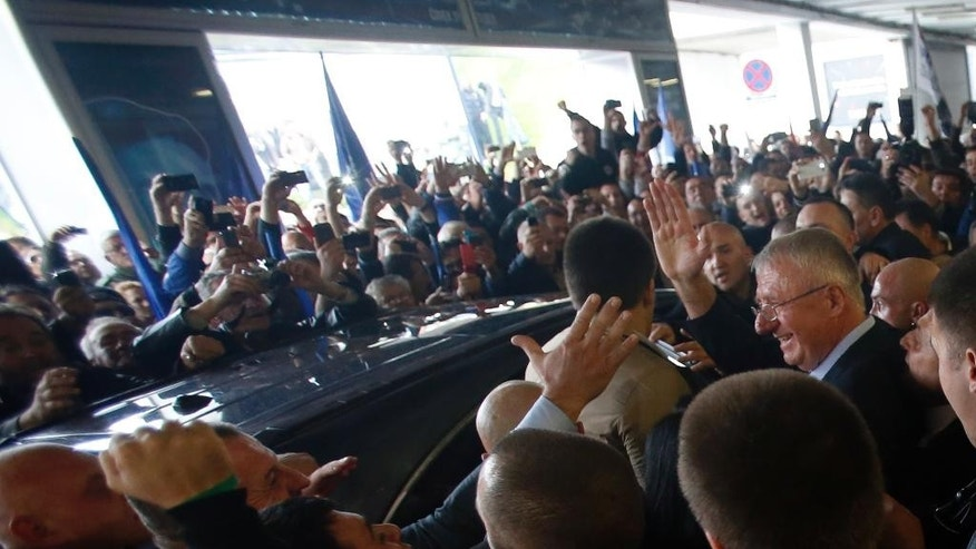 Serbian ultranationalist leader Vojislav Seselj, right, waves to his supporters upon  landing at Belgrade airport from The Hague, Netherlands Wednesday, Nov. 12, 2014.  Serbian far-right leader Vojislav Seselj, accused of recruiting notorious paramilitary forces during the Balkan wars in the 1990s, arrived home to a boisterous welcome by his supporters after United Nations war crimes judges approved his provisional release because of his ailing health.  (AP Photo/Darko Vojinovic).