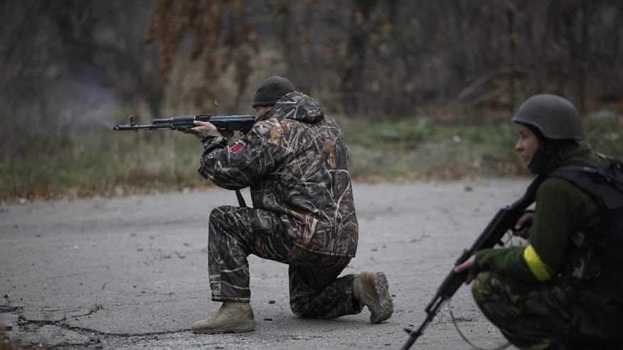 Ukrainian volunteer fighters shoot in the village of Peski near Donetsk, eastern Ukraine, Wednesday, Nov. 12, 2014. Fighting has continued in the east despite a cease-fire agreement between Ukraine and the rebels signed in September, and Ukraine and the West accused Russia recently of sending in new troops and weapons.  (AP Photo/Maxim Vetrov)