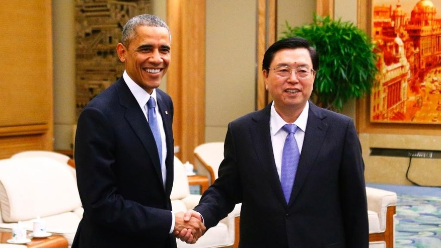 U.S. President Barack Obama, left, shakes hands with Chairman of the Standing Committee of the National People's Congress (NPC) Zhang Dejiang during a meeting at the Great Hall of the People in Beijing Wednesday, Nov. 12, 2014. (AP Photo/Petar Kujundzic, Pool)