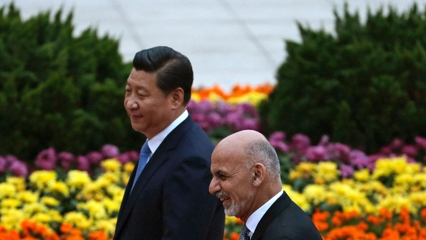 FILE - In this Oct. 28, 2014, file photo, Afghanistan President Ashraf Ghani, right, walks with his Chinese counterpart Xi Jinping after inspecting a guard of honor during a welcome ceremony outside the Great Hall of the People in Beijing. Ghani will make his first state visit to neighboring Pakistan in coming days, long blamed by his predecessor for harboring militants, in hopes of finding a way to revive peace talks with the Taliban. His third trip abroad after recently visiting Saudi Arabia and China appears part of his plan to recalibrate Afghanistan's relations with its neighbor as others pressure it over the militants hiding within its borders. (AP Photo/Andy Wong, File)