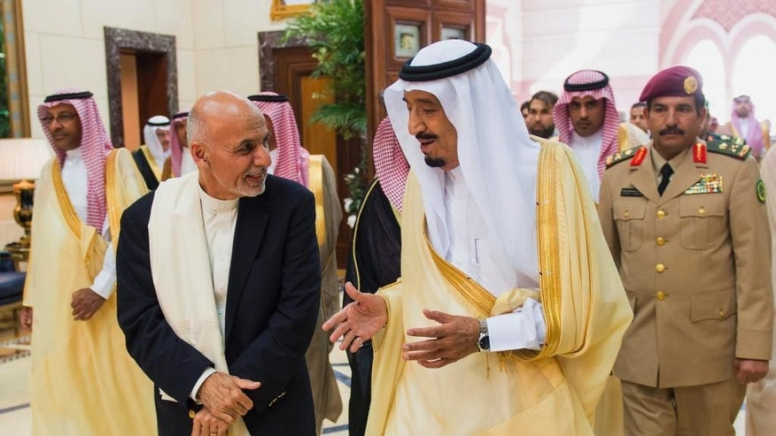 FILE - In this Oct. 26, 2014, file photo provided by the Saudi Press Agency, Saudi Arabia's Crown Prince Salman bin Abdulaziz Al Saud, center, talks with Afghanistan's President Ashraf Ghani in Riyadh, Saudi Arabia. Ghani will make his first state visit to neighboring Pakistan in coming days, long blamed by his predecessor for harboring militants, in hopes of finding a way to revive peace talks with the Taliban. His third trip abroad after recently visiting Saudi Arabia and China appears part of his plan to recalibrate Afghanistan's relations with its neighbor as others pressure it over the militants hiding within its borders. (AP Photo/Saudi Press Agency, File)