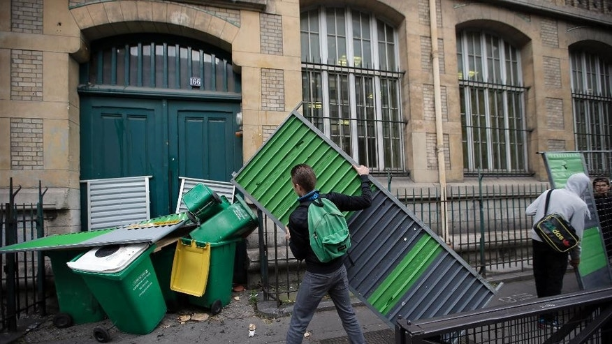 Students carry garbage cans and barriers to block the entrance of Paris Buffon high school, in Paris, France, Thursday, Nov. 13, 2014. Students block high schools around Paris in protest against authorities and in solidarity with Remi Fraisse, a 21-year-old environmental activist who died during clashes between security forces and protesters of the Sivens dam project. (AP Photo/Francois Mori)