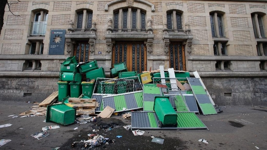 Garbage cans and barriers block the entrance to Paris Buffon high school, in Paris, France, Thursday, Nov. 13, 2014. Students block high schools around Paris in protest against authorities and in solidarity with Remi Fraisse, a 21-year-old environmental activist who died during clashes between security forces and protesters of the Sivens dam project. (AP Photo/Francois Mori)