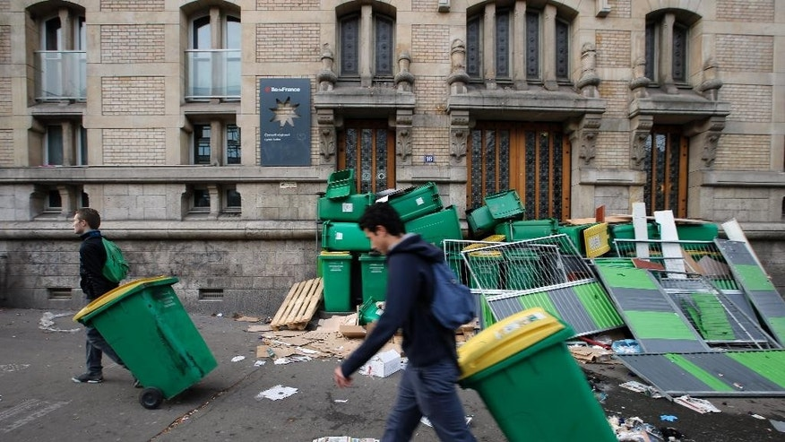 Students move garbage cans to block the entrance of Paris Buffon high school, in Paris, France, Thursday, Nov. 13, 2014. Students block high schools around Paris in protest against authorities and in solidarity with Remi Fraisse, a 21-year-old environmental activist who died during clashes between security forces and protesters of the Sivens dam project. (AP Photo/Francois Mori)