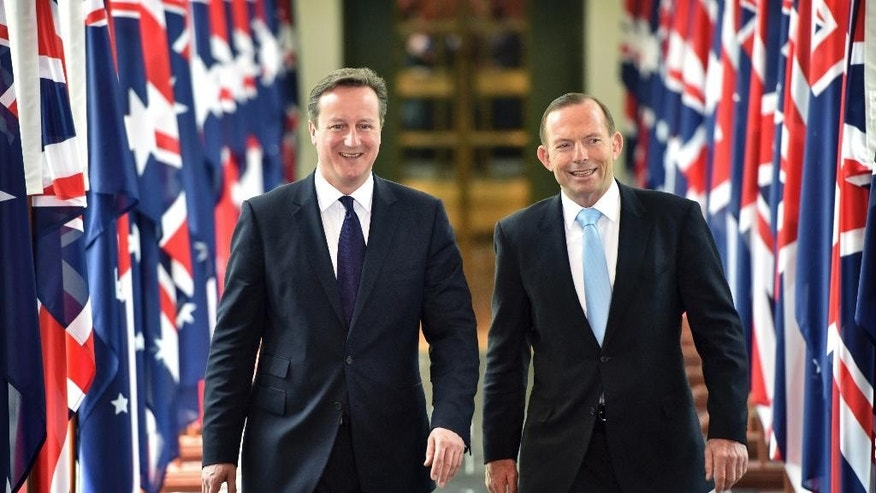 British Prime Minister David Cameron, left, walks with Australian Prime Minister Tony Abbott as they leave the house of representatives at Parliament House in Canberra, Friday, Nov. 14, 2014. Cameron is visiting Australia to attend the G20 summit. (AP Photo/Mark Graham, Pool)