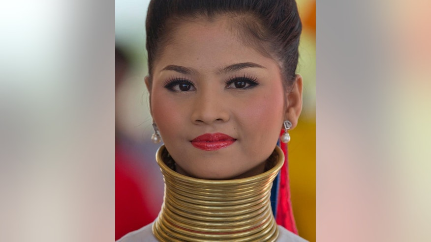 A woman in look-a-like ethnic Kayan-Padaung attire, with a fake copper neck ring, stands to welcome leaders attending the East Asia Summit at Myanmar International Convention Center in Naypyitaw, Myanmar, Thursday, Nov. 13, 2014. Women welcoming world leaders stand in rows, colorfully clad in costumes representing Myanmar's many ethnic groups, some with their hair tied in high knots or wrapped in red headdresses, others donning horizontally striped longyis and silver coin-studded capes. But none of the ushers belong to any of the minority groups they represent.  (AP Photo/Gemunu Amarasinghe)
