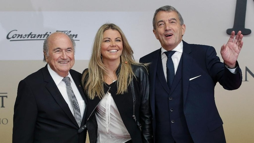 Wolfgang Niersbach, President of the German Soccer Association (DFB), right, FIFA President Sepp Blatter, left, and Niersbach's partner Marion Popp, center, pose for the media as they arrive for the premiere of the movie 'Die Mannschaft' (The Team) in Berlin, Germany, Monday, Nov. 10, 2014. (AP Photo/Michael Sohn)