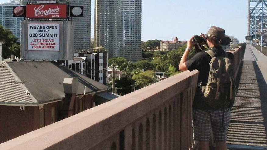 In this Nov. 8, 2014 photo, a man photographs a sign on the Story Bridge Hotel near the venue where the G20 leaders' summit will take place in Brisbane, Australia. For the boosters of Queensland state, playing host to top officials from the 20 biggest industrialized and developing economies is a long overdue acknowledgement they don't live in subtropical backwater. Small businesses, however, are struggling against the disruptions of road closures and an over-the-top security response. (AP Photo/Rod McGuirk)