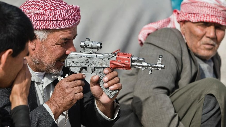 Syrian Kurdish refugee men from the Kobani area, play with a toy weapon at a camp in Suruc, on the Turkey-Syria border Thursday, Nov. 13, 2014. Kobani, also known as Ayn Arab, and its surrounding areas, has been under assault by extremists of the Islamic State group since mid-September and is being defended by Kurdish fighters. (AP Photo/Vadim Ghirda)