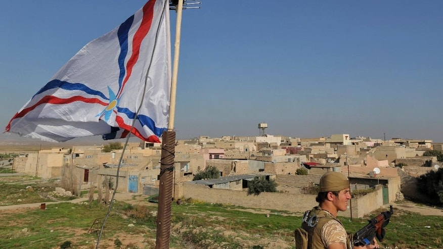 A Dwekh Nawsha militia member stands next to a flag of the Assyrian Patriotic Party, as he stands guard on the rooftop of a building in the Christian village of Bakufa, 30 kilometers (18.6 miles) north of Mosul, Iraq, Wednesday, Nov. 12, 2014. The party flag has replaced the black flag of the Sunni militants of the Islamic State group and is waving on the roof of the building at the entrance to the village. (AP Photo/Bram Janssen)