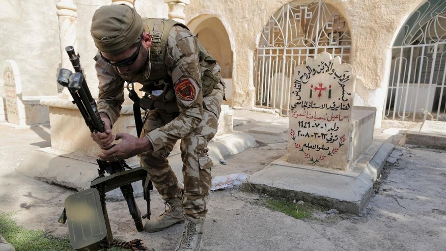 A Dwekh Naswha militia member prepares his weapon in front of a grave inside a 200-year-old monastery in the Christian village of Bakufa, 30 kilometers (18.6 miles) north of Mosul, Iraq, Wednesday, Nov. 12, 2014. The recently-formed Christian militia group has taken control of the northern Iraqi town of Bakufa, which, just until over a month ago, was in the hands of extremists from the Islamic State group. (AP Photo/Bram Janssen)