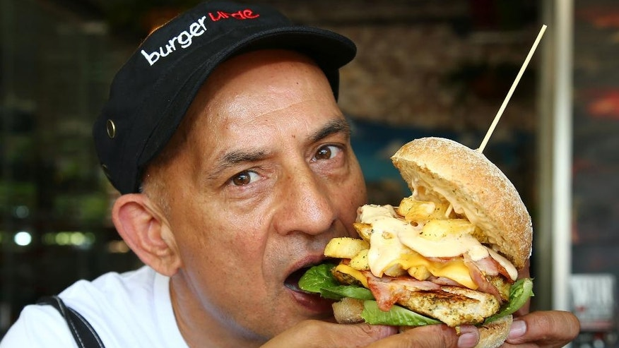 "Burger shop owner Balwinder Kalley prepares to take a bite of a ""Big Bad Vlad"" burger which is for sale during this weekend's G-20 summit in Brisbane, Australia, Friday, November 14, 2014. From ""The Big Bad Vlad"" to the ""Obamarama Burger,"" local restaurants and pubs are cashing in on the event by offering G-20-themed goodies.(AP Photo/Tertius Pickard)"