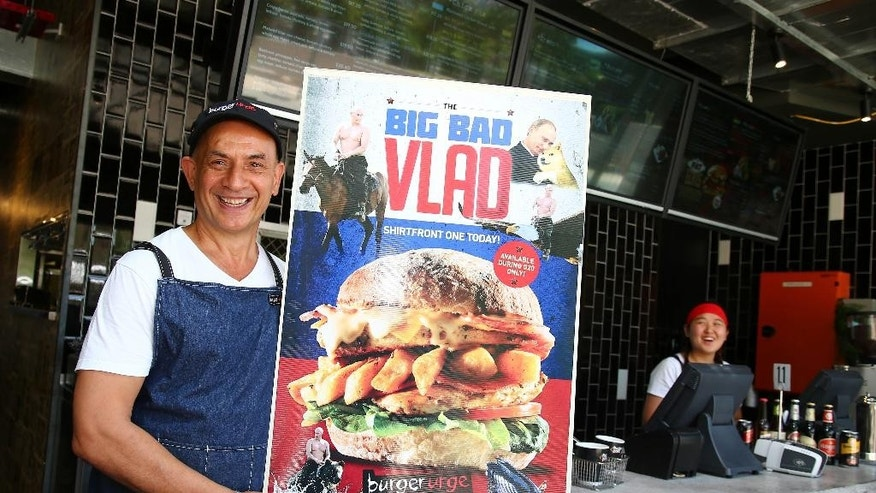 "Burger shop owner Balwinder Kalley holds a poster promoting the ""Big Bad Vlad"" burger which is for sale during this weekend's G-20 summit in Brisbane, Australia, Friday, November 14, 2014. From ""The Big Bad Vlad"" to the ""Obamarama Burger,"" local restaurants and pubs are cashing in on the event by offering G-20-themed goodies. (AP Photo/Tertius Pickard)"
