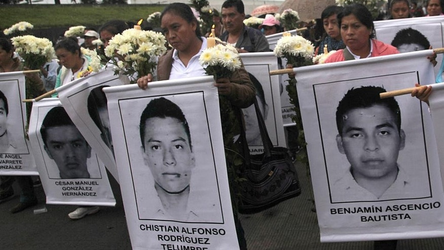 "In this Oct. 19, 2014 photo, Maria Telumbre, center, walks with a poster emblazoned with the image of her missing 19-year-old son, to the Basilica of Guadalupe for a special Mass, in Mexico City. The discovery of charred teeth and bone fragments in plastic garbage bags offered Telumbre no more proof of her son's death than the many graves unearthed in Guerrero state since the students disappeared Sept. 26. Nor did it cause her ""enormous pain"" as Attorney General Jesus Murillo Karam said it would, because she did not accept that the ashes belonged to her son and his classmates. (AP Photo/Marco Ugarte)"