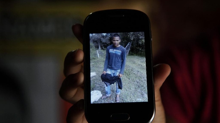 In this Nov. 9, 2014 photo, the godmother of missing student Christian Rodriguez Telumbre, shows an image of Christian on her cellphone, in Tixtla, Mexico. Christian told his family he wanted a higher education to help support them. He had hoped to study agronomy at a university, but the family didn't have the money. His only option was the tuition-free teacher's college, known for Spartan living and radical politics dating back to the Mexican Revolution, the Rural Normal School of Ayotzinapa. (AP Photo/Marco Ugarte)