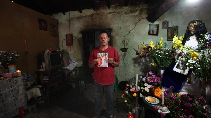 In this Nov. 9, 2014 photo, Clemente Rodriguez holds a photo of his missing son Christian Rodriguez Telumbre during an interview in his home in Tixtla, Mexico. The 19-year-old son of Rodriguez is one of the 43 Rural Normal School of Ayotzinapa students who were last seen in the custody of police in the city of Iguala, allegedly at the behest of the mayor. Rodriguez and his wife hold fast to the belief that their son who loved folk dancing is alive. (AP Photo/Marco Ugarte)