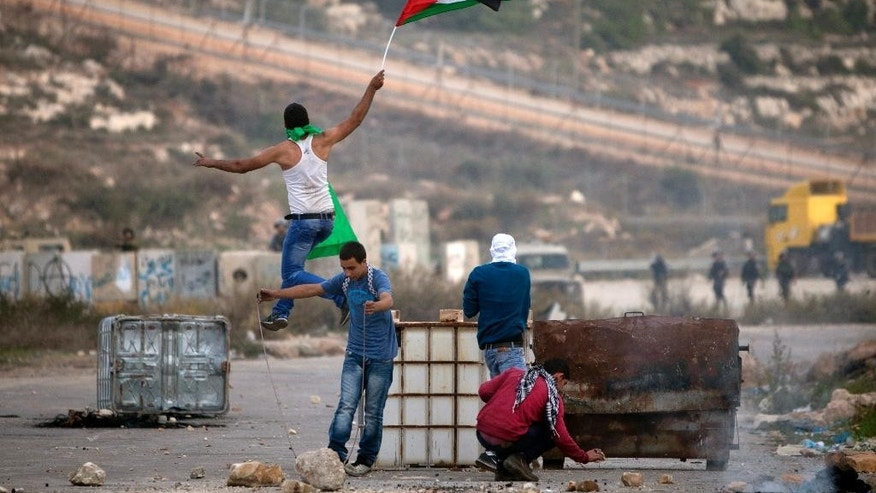 "A Palestinian demonstrator holding a national flag jumps during clashes with Israeli soldiers, outside the Ofer military prison, near the West Bank city of Ramallah, Tuesday, Nov. 11, 2014. The Palestinian president on Tuesday accused Israel of provoking a ""religious war"" as new violence between the sides broke out in the West Bank, leaving a Palestinian man dead, amid mounting concerns that the long-running conflict is entering a new and dangerous phase. The new spate of violence comes amid rising tensions spawned by conflicting claims to the Jerusalem holy site known to Jews as the Temple Mount and Muslims as the Noble Sanctuary and the aftermath of this summer's bloody Gaza war, in which more than 2,100 Palestinians and 72 people on the Israeli side were killed. (AP Photo/Majdi Mohammed)"