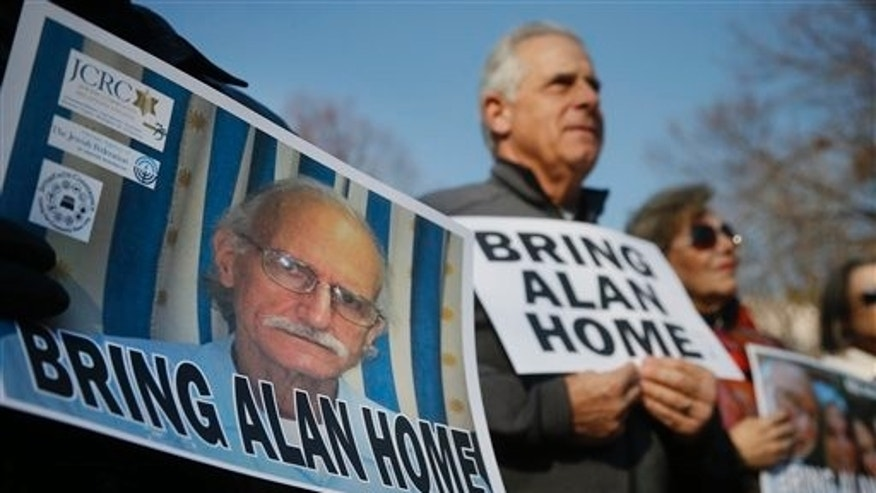 FILE - In this Dec. 3, 2013 file photo, supporters of Alan Gross, on poster at left, mark his fourth year in a Cuban prison with a protest in Lafayette Park, across from the White House in Washington D.C. Two U.S. senators said Tuesday, Nov. 11, 2014 that they're optimistic that the imprisoned American government contractor will be freed. Sens. Jeff Flake of Arizona and Tom Udall of New Mexico said in Havana that they met Gross for about two hours during a trip that included meetings with Cuban officials. Gross was detained in December 2009 while working to set up Internet access as a subcontractor for the U.S. government's U.S. Agency for International Development. He was tried and sentenced to 15 years in prison. (AP Photo/Charles Dharapak, File)