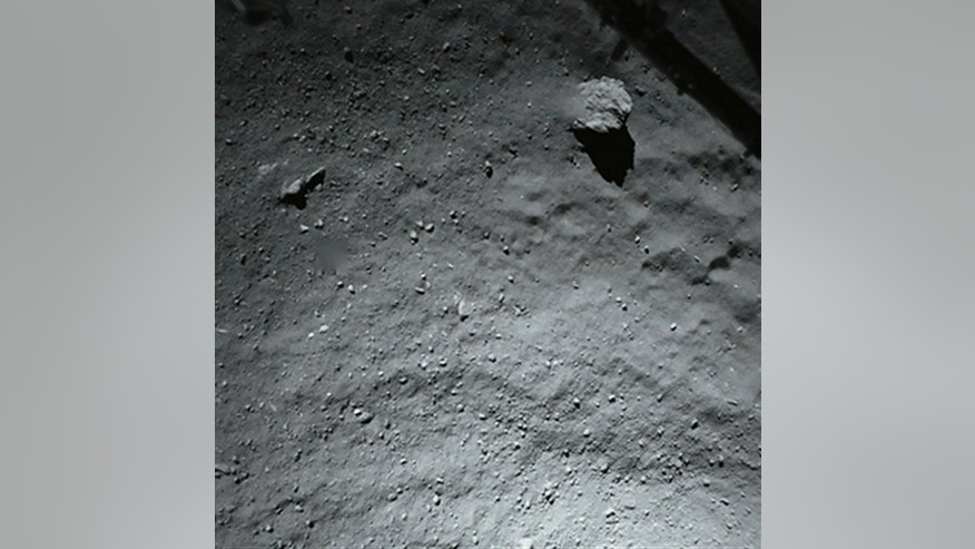 This image released by the European Space Agency ESA Thursday Nov. 13, 2014 was taken by Philae's down-looking descent ROLIS imager when it was about 40 meters (131 feet) above the surface of Comet 67P/Churyumov-Gerasimenko Wednesday.  It shows that the surface of the comet is covered by dust and debris ranging from mm to metre sizes The large block in the top right corner is 5 m in size. In the same corner the structure of the Philae landing gear is visible.  The lander scored a historic first Wednesday, touching down on comet 67P/Churyumov-Gerasimenko after a decade-long, 6.4 billion-kilometer (4 billion-mile) journey through space aboard its mother ship, Rosetta. The comet is streaking through space at 41,000 mph (66,000 kph) some 311 million miles (500 million kilometers) from Earth.  (AP Photo/Esa,Rosetta,Philae)