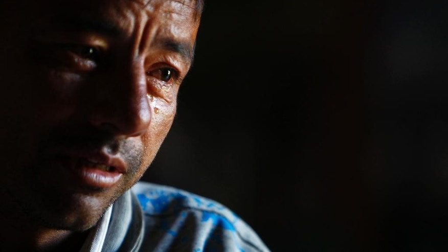 In this Sunday, Nov. 2, 2014 photo, Kumar Budathoki, who sold one of his kidneys to organ traffickers, cries as he narrates his story in Hokse, a village of tiny farms and mud huts that has been the center of the illegal organ trade in Nepal for more than a decade. Under crushing financial strain, Budathoki sold one of his kidneys to organ traffickers for $5,000, a sum he hoped would help set him up for a lifetime free of money problems. Instead, he got a lifetime of health problems - and only a fraction of the money promised to him by a shady broker in Hokshe, a village of tiny farms and mud huts that has been the center of the illegal organ trade in Nepal for more than a decade. (AP Photo/ Niranjan Shrestha)