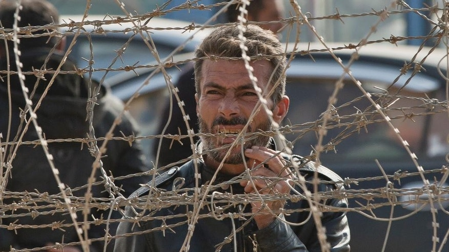 A Syrian Kurdish man stands behind a barbed wire fence that marks the Turkey-Syria border on the outskirts of Kobani, seen from the Turkish side of the border outside the village of Yumurtalik on the Friday, Nov. 14, 2014. Kobani, also known as Ayn Arab, and its surrounding areas, has been under assault by extremists of the Islamic State group since mid-September and is being defended by Kurdish fighters. (AP Photo/Vadim Ghirda)