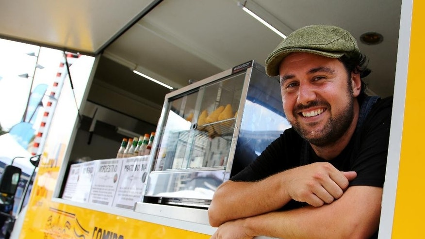"In this Thursday, Nov. 13, 2014 photo, Brazilian food truck owner Carlo Xavier waits for customers ahead of the G-20 conference in Brisbane, Australia. Xavier said, ""The G-20 I think has been good so far, we have gained a lot of business today in King George Square, so far it's been good."" (AP Photo/Mark Baker)"