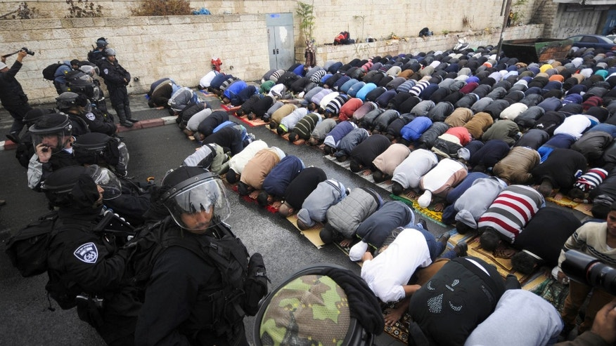 Oct. 31, 2014: Israeli border police block a road as Palestinians pray in Jerusalem