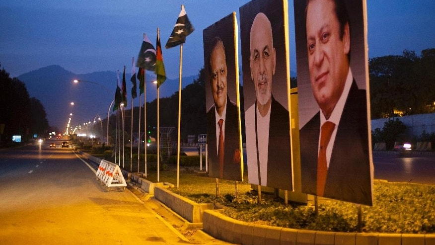 Billboards show photographs of Pakistani Prime Minister Nawaz Sharif, from right, Afghan President Ashraf Ghani and Pakistani President Mamnoon Hussain ahead of Ghani's visit, as displayed on the median of a street in Islamabad, Pakistan, Thursday, Nov. 13, 2014. Ghani will make his first state visit in coming days to neighboring Pakistan, long blamed by his predecessor for harboring militants, in hopes of finding a way to revive peace talks with the Taliban. (AP Photo/B.K. Bangash)