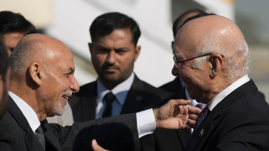Pakistan's adviser on National Security and  Foreign Affairs Sartaj Aziz, right, greets Afghan President Ashraf Ghani at Chaklala airbase in Rawalpindi, Pakistan, Friday, Nov. 14, 2014. Ghani makes his first state visit to neighboring Pakistan, long blamed by his predecessor for harboring militants, in hopes of finding a way to revive peace talks with the Taliban. (AP Photo/B.K. Bangash)