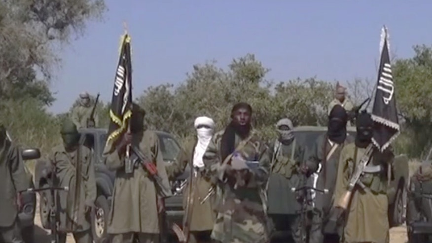Oct. 31, 2014 - FILE still (from video) of the leader of Nigeria's Islamic extremist group Boko Haram, center, who has denied agreeing to any cease-fire with the government. Islamic extremists in Nigeria have seized Chibok, forcing thousands of residents to flee. Insurgents kidnapped nearly 300 schoolgirls from the town in April.
