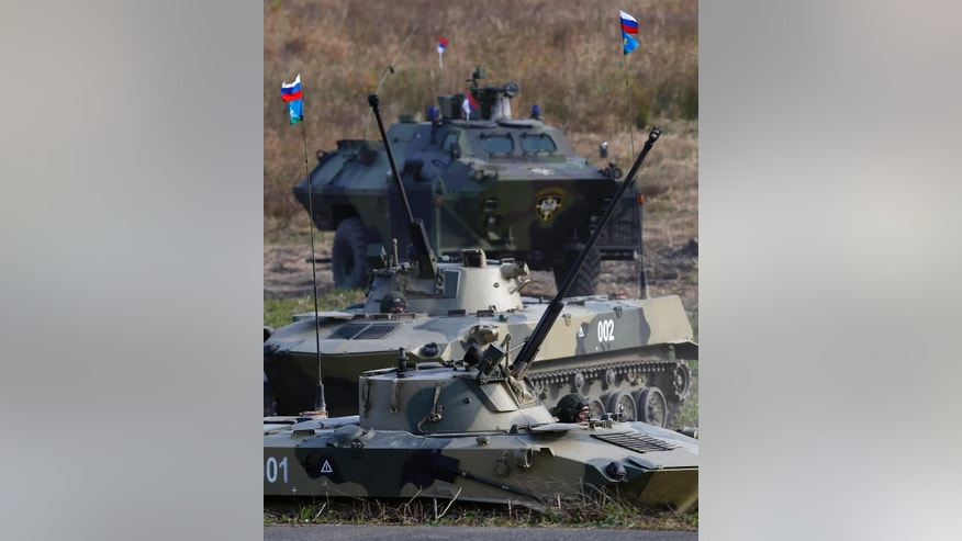 During a military exercise two Russian airborne infantry fighting vehicles BMD-2, front and an Serbian armored personnel carrier roar during the Russian-Serbian joint antiterrorist exercise Srem 2014, at Nikinci training ground, 60 kilometers west of Belgrade, Serbia, Friday, Nov. 14, 2014. (AP Photo/Darko Vojinovic)