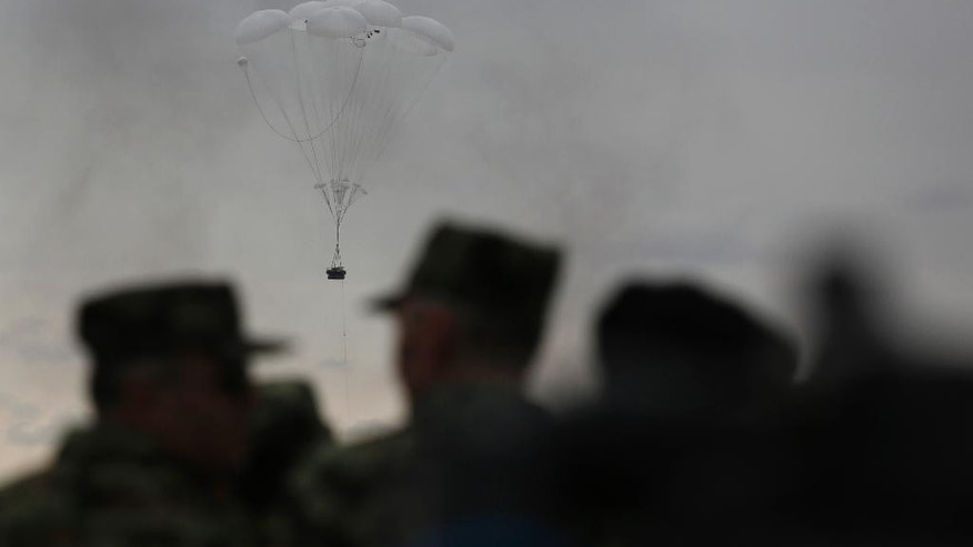 Russian and Serbian officers observe an airborne infantry fighting vehicle being parachuted from a plane during the Russian-Serbian joint antiterrorist exercise Srem 2014, at Nikinci training ground, 60 kilometers west of Belgrade, Serbia, Friday, Nov. 14, 2014. (AP Photo/Darko Vojinovic)