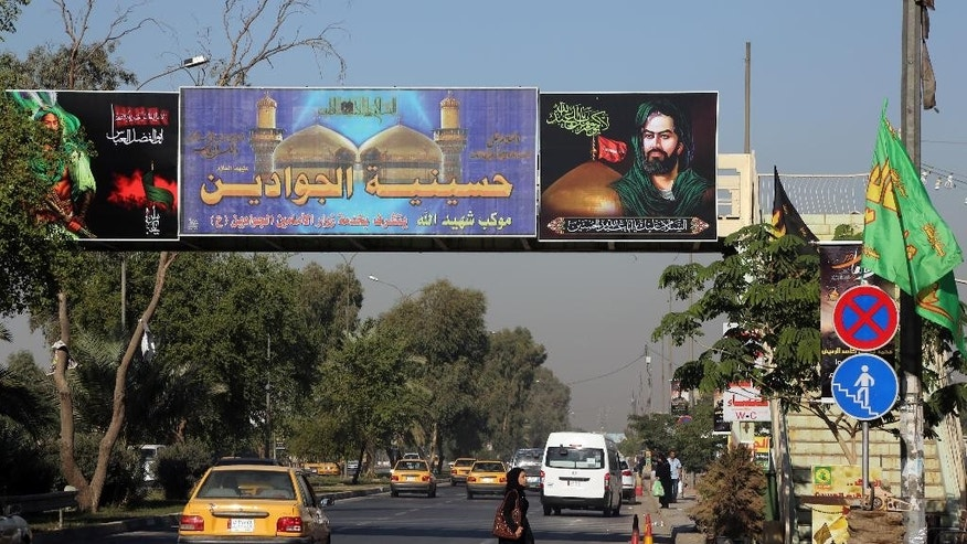 In this Monday, Nov. 10, 2014 photo, people pass under Shiite banners in Ghadeer district in southeastern Baghdad, Iraq. Religious banners and portraits of Imam Hussein, a grandson of the Prophet Muhammad, hang from homes, bridges, stores and even colleges across much of Baghdad and can be seen even in Sunni-majority areas. They also adorn government buildings and hundreds of security checkpoints across the city, reinforcing Sunni fears that Shiite Prime Minister Haider al-Abadi is no less sectarian than his predecessor Nouri al-Maliki, whose policies were widely seen as aggravating Sunni grievances. (AP Photo/Karim Kadim)
