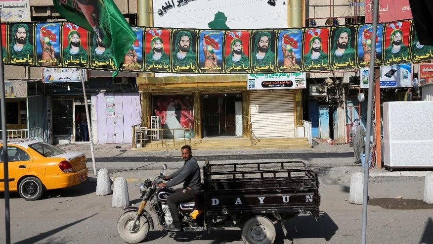 In this Monday, Nov. 10, 2014 photo, a motorcycle passes by banners of religious leaders of Shiites in Sadr City Baghdad, Iraq. Religious banners and portraits of Imam Hussein, a grandson of the Prophet Muhammad, hang from homes, bridges, stores and even colleges across much of Baghdad and can be seen even in Sunni-majority areas. They also adorn government buildings and hundreds of security checkpoints across the city, reinforcing Sunni fears that Shiite Prime Minister Haider al-Abadi is no less sectarian than his predecessor Nouri al-Maliki, whose policies were widely seen as aggravating Sunni grievances. (AP Photo/Karim Kadim)