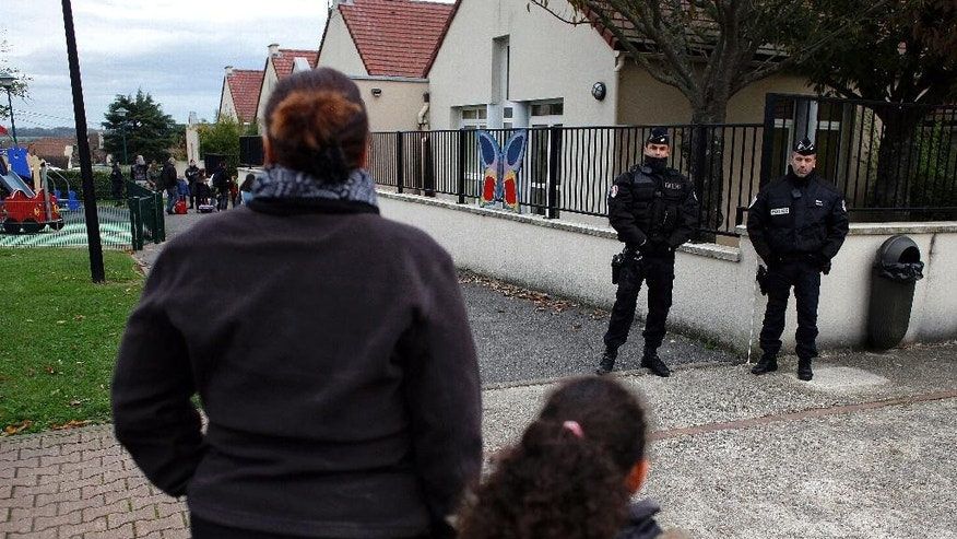 Police officers stand next to a school in Montevrain, east of Paris, Friday Nov. 14, 2014. Scores of police patrolled a small town west of the French capital on Thursday night after a tiger eluded a massive search and remained on the prowl in the region near Disneyland Paris. (AP Photo/Thibault Camus)