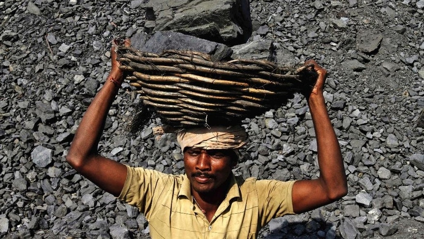 In this Thursday, Nov. 13, 2014 photo, an Indian daily wage laborer holds a basket filled with coal on his head as he works at a local coal depot on the outskirts of Cuttack, 25 kilometers (16 miles) from the eastern Indian city of Bhubaneswar, India. This week's China-U.S. climate agreement between the world's top two polluters puts pressure on India, No. 3 on the list, to become more energy efficient and should encourage investment in renewable energy. (AP Photo/Biswaranjan Rout)