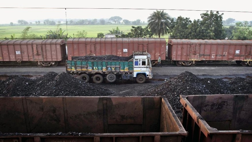 In this Thursday, Nov. 13, 2014 photo, a truck loaded with coal stands at a railway station on the outskirts of Cuttack, 25 kilometers (16 miles) from the eastern Indian city of Bhubaneswar, India. This week's China-U.S. climate agreement between the world's top two polluters puts pressure on India, No. 3 on the list, to become more energy efficient and should encourage investment in renewable energy. (AP Photo/Biswaranjan Rout)