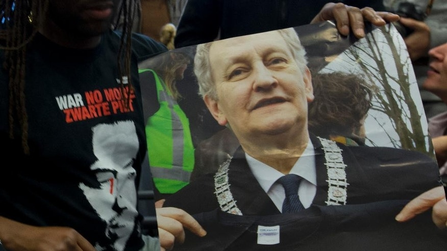 "People wearing T-shirts reading ""World Against Racism, No More Black Pete"" and holding a poster with a picture of Amsterdam mayor Eberhard van der Laan attend the ruling over a complaint that the city of Amsterdam had no right to authorize a parade with Black Pete because he is a negative stereotype of black people, at the highest Dutch administrative in The Hague, Netherlands, Wednesday, Nov. 12, 2014. The court declined to wade into the increasingly acrimonious national debate around Black Pete, the black-faced sidekick to the Dutch equivalent of Santa Claus, and ruled that the city of Amsterdam was right to grant a permit for parade with Black Petes. (AP Photo/Peter Dejong)"