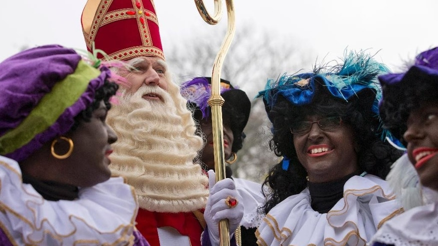 "FILE - In this Nov. 16, 2013 file photo the Dutch version of Santa Claus, Sinterklaas, or Saint Nicholas, and his sidekicks known as  ""Zwarte Piet"" or ""Black Pete"" arrive by steamboat in Hoorn, north-western Netherlands. The ruling over a complaint that the city of Amsterdam had no right to authorize a parade with Black Pete because he is a negative stereotype of black people, took place at the highest Dutch administrative in The Hague on Wednesday, Nov. 12, 2014. The court declined to wade into the increasingly acrimonious national debate around Black Pete, the black-faced sidekick to the Dutch equivalent of Santa Claus, and ruled that the city of Amsterdam was right to grant a permit for parade with Black Petes. (AP Photo/Peter Dejong, File)"