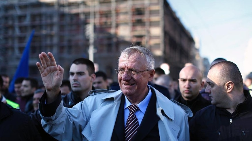 Serbian far right leader, Vojislav Seselj, center, waves to his supporters at a rally in Belgrade, Serbia, Saturday, Nov. 15, 2014. Several thousand supporters gathered in Belgrade on Saturday in support of Seselj, who is accused of recruiting notorious paramilitary forces during the bloody Balkan wars, and has returned home on a provisional release from the UN war crimes court. (AP Photo/Marko Drobnjakovic)