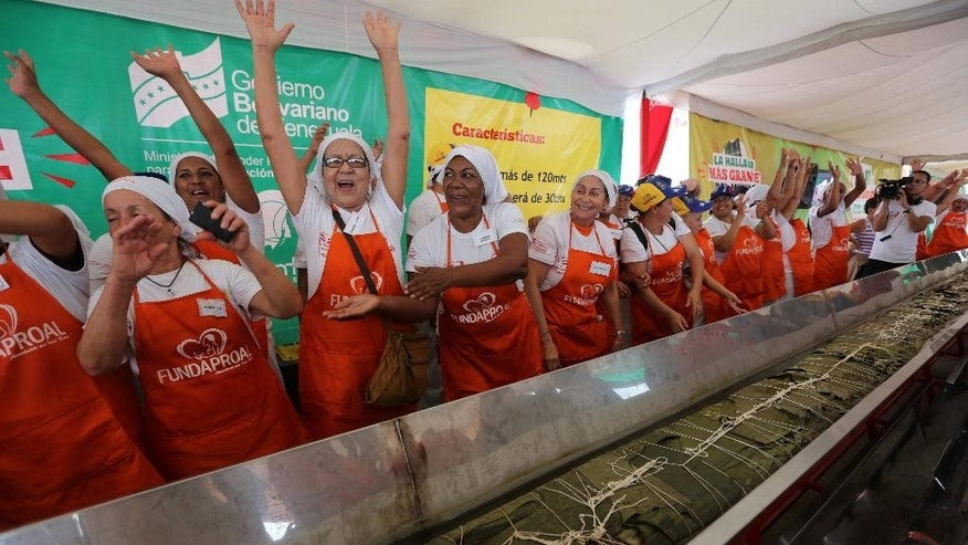 Women cheer after preparing the world's largest hallaca, which features pork, beef, chicken, olives and raisins folded into corn dough and wrapped in a banana leaf, in Caracas, Venezuela, Saturday, Nov. 15, 2014. With some help from the Ministry of Nutrition, the South American country set a record for the world's biggest hallaca, a local take on the tamale traditionally eaten in December. The Guinness book of world records certified the nearly 400-foot creation as the world's largest. (AP Photo/Ariana Cubillos)