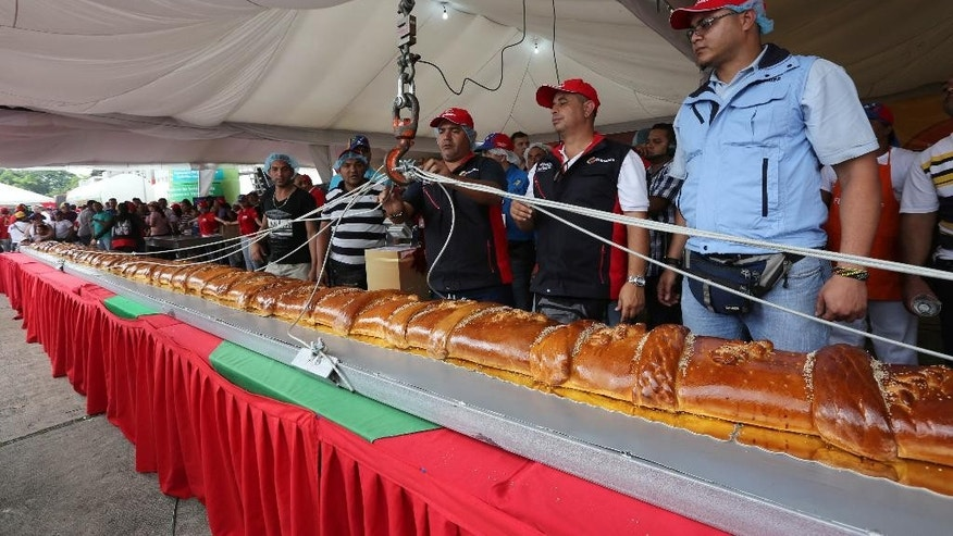 Officials weigh the world's largest Pan de Jamón in Caracas, Venezuela, Saturday, Nov. 15, 2014. Hundreds of cooks and spectators were on hand for the creation of the Pan de Jamón, a Christmas specialty in which ham is rolled in sweet bread, as well as the world's biggest hallaca, a local take on the tamale traditionally eaten in December. (AP Photo/Ariana Cubillos (AP Photo/Ariana Cubillos)